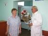 Букет тысячному пациенту вручает директор В.Ф. Юдаков